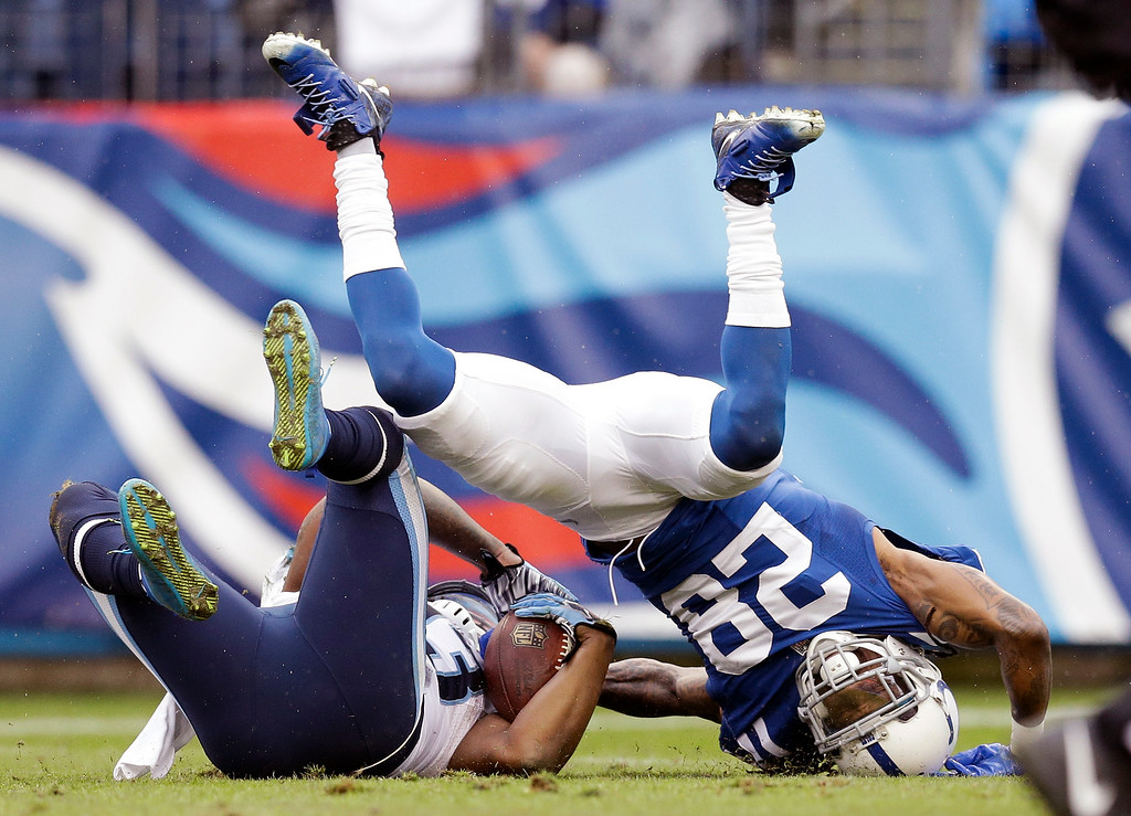 . Tennessee Titans running back Shonn Greene, left, is stopped by Indianapolis Colts cornerback Greg Toler (28) after running the ball for a 52-yard gain in the second half of an NFL football game Sunday, Dec. 28, 2014, in Nashville, Tenn. (AP Photo/Sanford Myers)