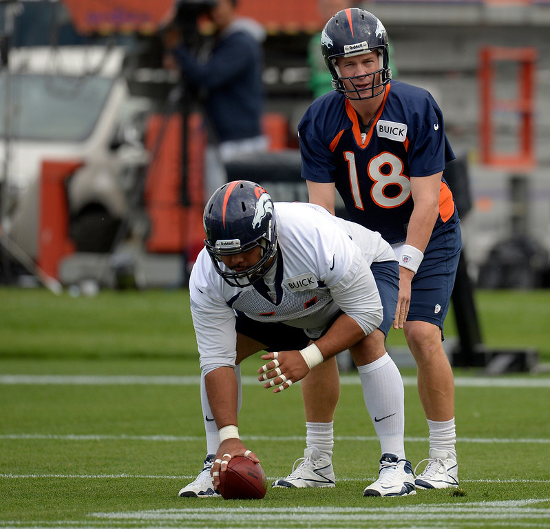 . Denver Broncos quarterback  Peyton Manning (18) starts off the day under center Manny Ramirez (66) during opening day of training camp July 25, 2013 at Dove Valley. (Photo By John Leyba/The Denver Post)