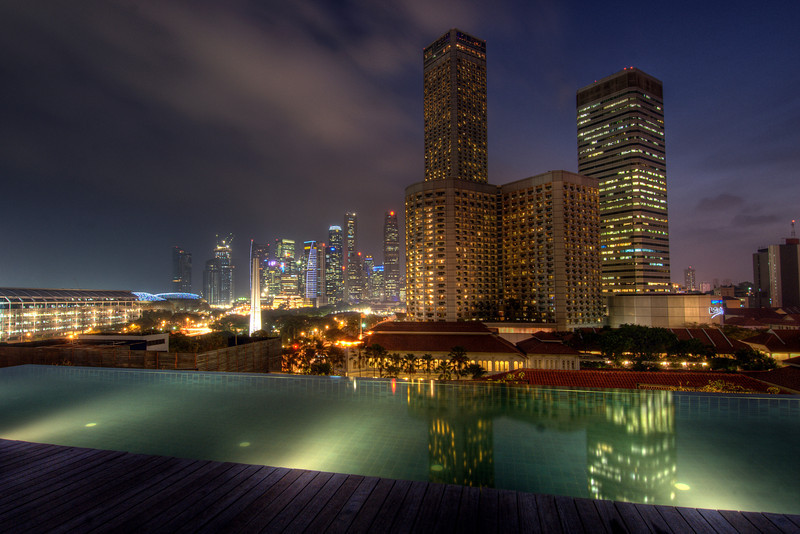 Infinity pool on rooftop and skyline at night - Singapore