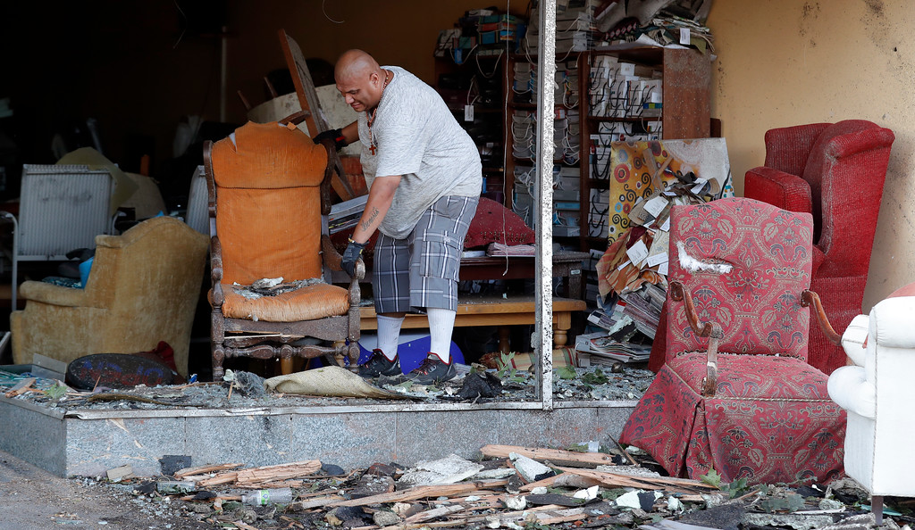 . Juan Moz, of Marshalltown, Iowa, helps clean out a tornado-damaged business on Main Street, Thursday, July 19, 2018, in Marshalltown, Iowa. Several buildings were damaged by a tornado in the main business district in town including the historic courthouse.(AP Photo/Charlie Neibergall)