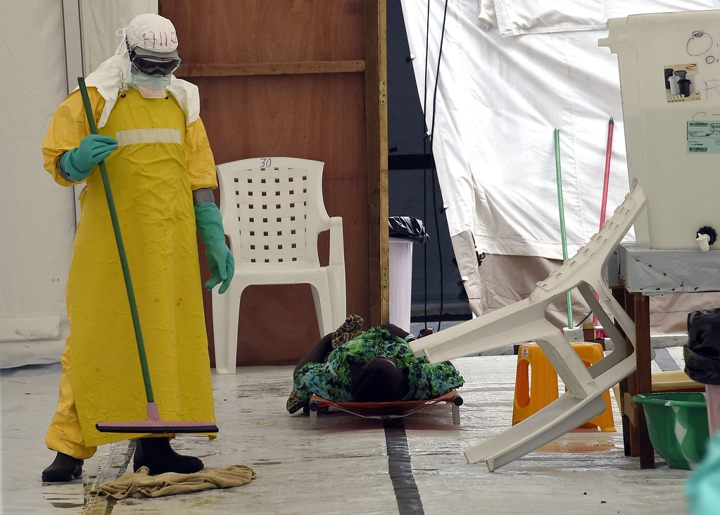 . A health worker cleans the floor as a man lies on a stretcher at the medical centre of Doctor Without Borders (Medecin sans Frontiere (MSF) where people infected with the Ebola virus are treated in Monrovia on September 26, 2014. PASCAL GUYOT/AFP/Getty Images