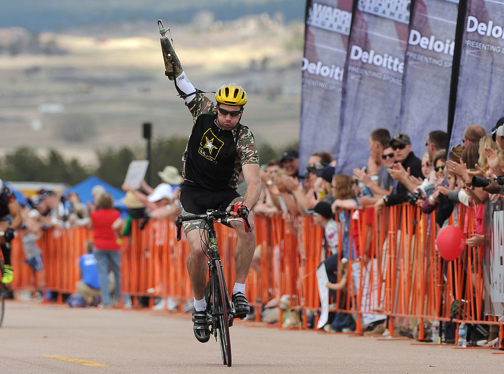 . Army National Guardsman JR Salzman raises his arm as he crosses the finish line 2nd in the  Men\'s 30K Bicycle Disability race.  He finished 52:50. The fourth annual Warrior Games cycling event took started and finished at Falcon Stadium on the grounds of the Air Force Academy in Colorado Springs, CO on May 12, 2013.  HRH Prince Harry was on hand to start the race as well as to hand out medals at the finish line.   A total of 260 wounded, ill and injured service members and veterans came to compete in the week long games.  Members of the Army, Marine Corps, Navy/Coast Guard/Air Force. Special Operations and the British Armed Forces all took part in the competition.  Other events included in the Warrior Games are shooting, sitting volleyball, track & field and wheelchair basketball.  (Photo by Helen H. Richardson/The Denver Post)