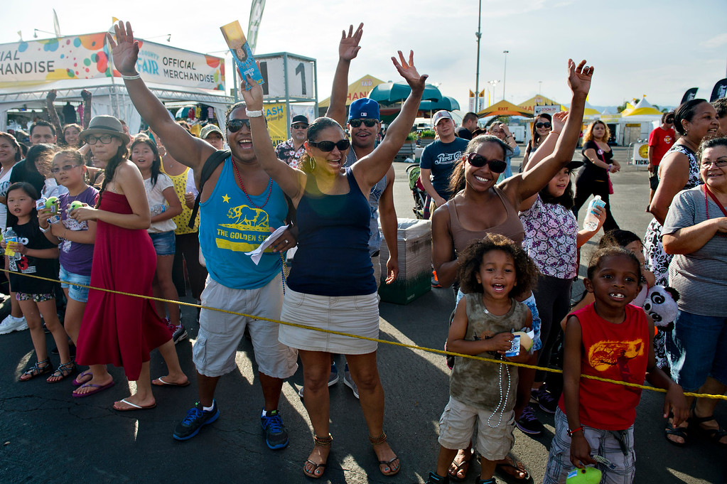 . Crowds wave at the fair parade during opening day of L.A. County Fair in Pomona on Friday, Aug. 30, 2013. (Staff photo by Watchara Phomicinda/ San Gabriel Valley Tribune)