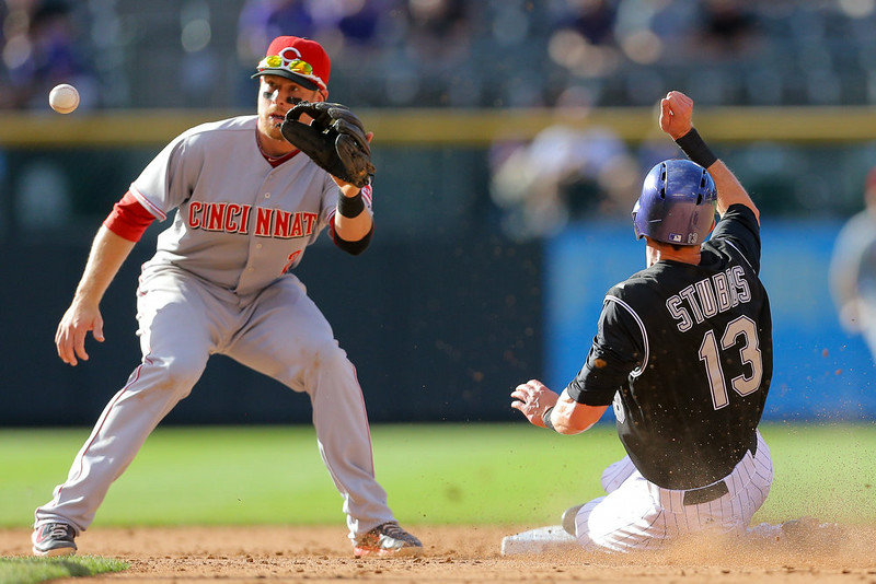 . Drew Stubbs #13 of the Colorado Rockies steals second base before short stop Zack Cozart #2 of the Cincinnati Reds can receive the throw during the eighth inning at Coors Field on August 17, 2014 in Denver, Colorado. The Rockies defeated the Reds 10-9. (Photo by Justin Edmonds/Getty Images)
