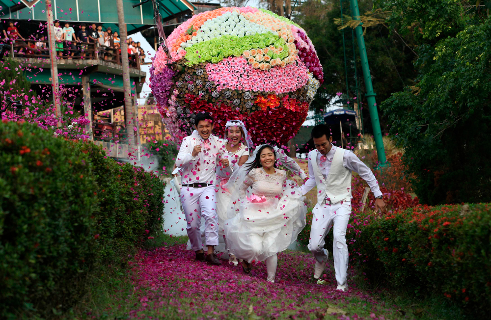 Description of . Thai grooms and their brides (L-R) Sorawich Changtor, 28, Rungnapa Panla, 30, Varuttaon Rangsiyawong, 27, and Prasit Rangsiyawong, 29, run during a wedding ceremony ahead of Valentine's Day in Prachin Buri province, east of Bangkok, February 13, 2013. Three Thai couples took part in the wedding ceremony arranged by a Thai resort, aimed to strengthen the relationships of the couples by doing fun activities.  REUTERS/Kerek Wongsa
