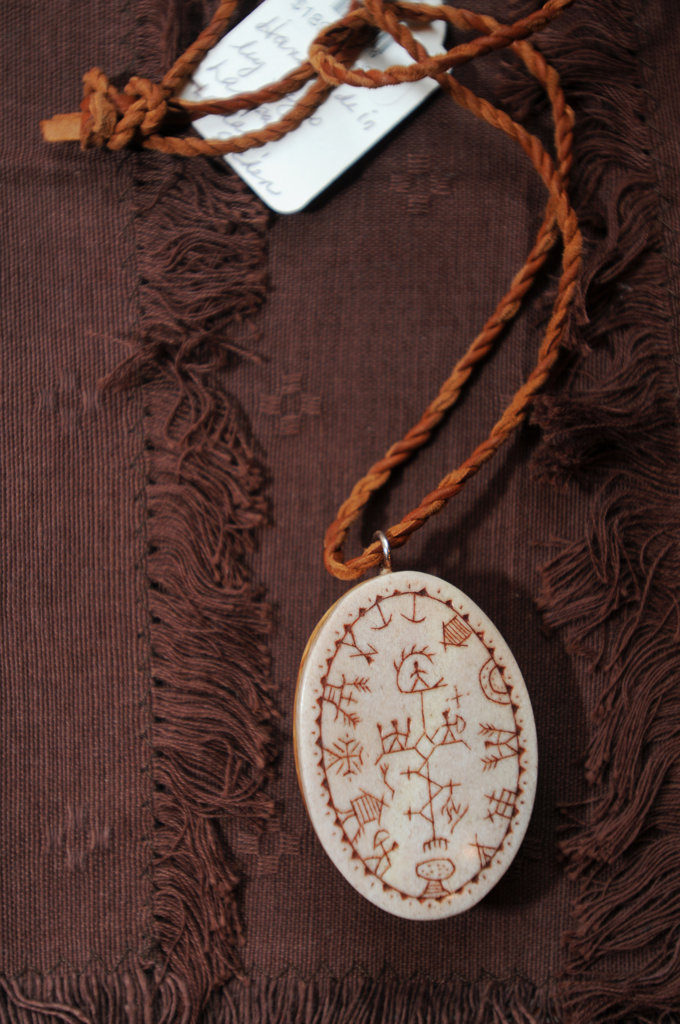 . A handmade necklace for sale at Ingebretsen\'s in Stockholm replicates a Sami drum with petroglyphs carved in reindeer bone with a base of birch wood  hanging on a  rope from reindeer hide. The necklace was made by Samis who live in  Sweden and Norway just above the Artic Circle. (Pioneer Press: Ginger Pinson)