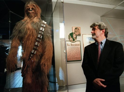 """. FILE - In this Oct. 29, 1997 file photo, filmmaker George Lucas looks over a Chewbacca costume at the \""""Star Wars\"""" exhibit at the Smithsonian Institution\'s Air and Space Museum in Washington. Actor Peter Mayhew, who is best known for his portrayal of Chewbacca in the \""""Star Wars\"""" films, has had double knee-replacement surgery at a Texas hospital.  (AP Photo/Ken Cedeno, File)"""