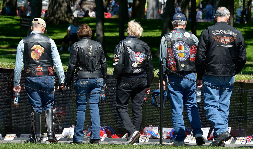 . Motorcycle riders view the names of the thousands of fallen military on the Vietnam Veterans Memorial, along with flowers, remembrances and keepsakes left by visitors, as they join hundreds of thousands of motorcycle riders on Memorial Day weekend for the 26th Annual Rolling Thunder Rally to remember POWs and MIAs from America\'s wars, in Washington, May 26, 2013.   REUTERS/Mike Theiler