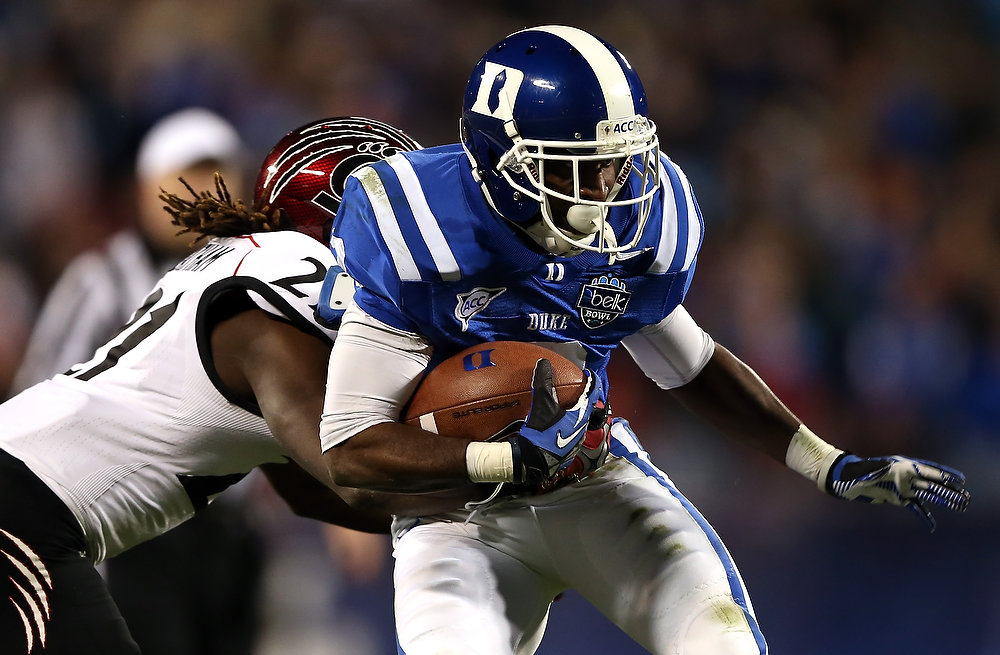 . Camerron Cheatham #21 of the Cincinnati Bearcats tries to stop Jamison Crowder #3 of the Duke Blue Devils during their game at Bank of America Stadium on December 27, 2012 in Charlotte, North Carolina.  (Photo by Streeter Lecka/Getty Images)