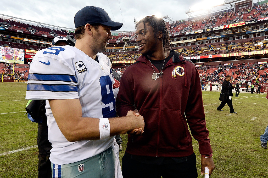 . Quarterback Tony Romo #9 of the Dallas Cowboys shakes hands with quarterback Robert Griffin III #10 of the Washington Redskins after the Cowboys defeated the Redskins 24-23 during an NFL game at FedExField on December 22, 2013 in Landover, Maryland.  (Photo by Patrick McDermott/Getty Images)