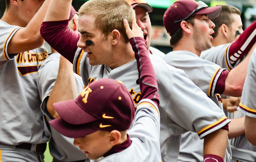 . Minnesota catcher Matt Halloran, center, is welcomed to the dugout by his teammates (and the ball boy) after hitting a three-run home run in the fifth inning. (Pioneer Press: Ben Garvin)