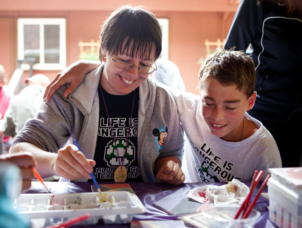 . Lisa Hargreaves of Sacramento, paints tiles with her son, Brendan, 13, during Camp ALWAYS at Mt. Cross in Ben Lomond, Calif., on Tuesday, June, 25, 2013.  (Patrick Tehan/Bay Area News Group)