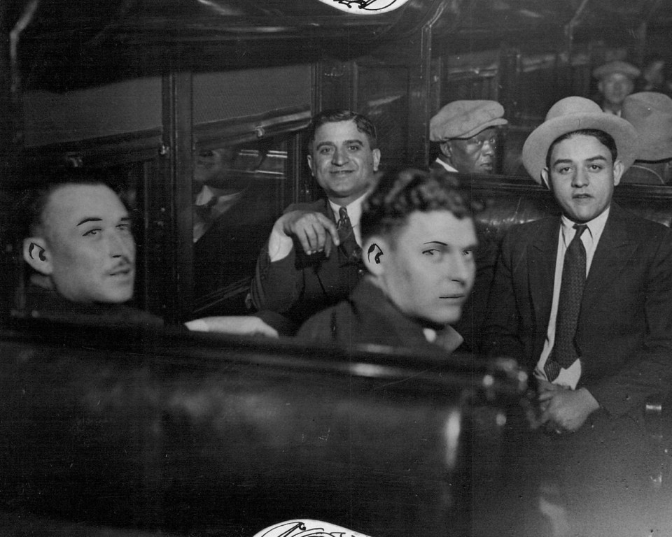 ". JUN 3 1932 - Prison-Bound Bootleggers constituted the majority of twenty-eight federal prisoners who were removed from the Denver county jail to the federal penitentiary at Leavenworth, Kan., Friday afternoon. Here are four ""big shots\"" of the rum business in Colorado, photographed in a prison car just before departure from the union station. Left to right, they are-Jack Ursetta, Roxie Stone, James Piccoli and James Marino. (Denver Post digital archive photo)"