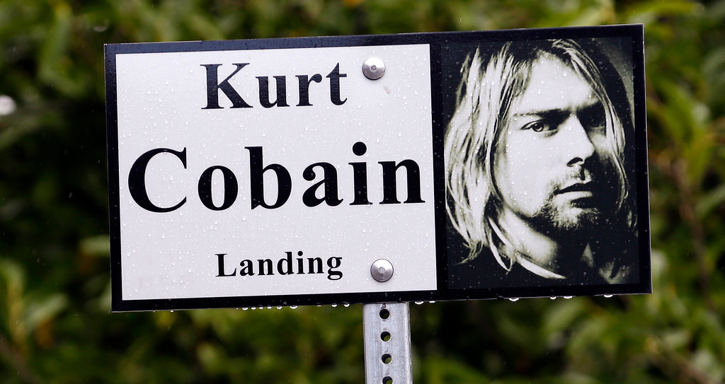 ". In this photo taken Monday, Sept. 23, 2013, a sign marks the location of ""Kurt Cobain Landing,\"" a tiny park blocks from the childhood home of Kurt Cobain, the late frontman of Nirvana, in Aberdeen, Wash.  (AP Photo/Elaine Thompson)"