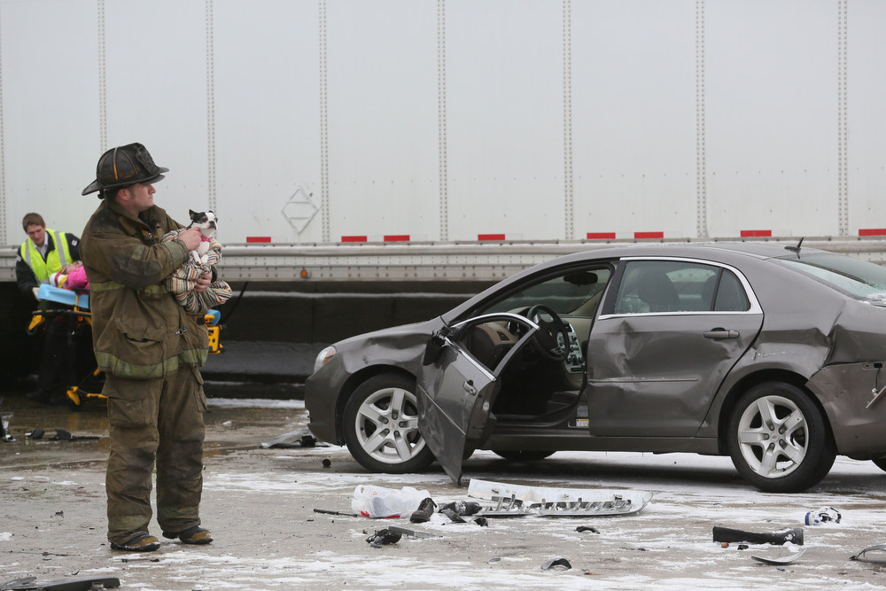 Description of . A firefighter holds a dog as its owner is removed from her car to be taken for medical treatment after a multi-vehicle accident on south bound I-75 in Detroit Thursday, Jan. 31, 2013. Snow squalls and slippery roads led to deadly accidents on a Detroit freeway Thursday, leaving at least two dead and about 20 injured on a mile-long stretch of roadway involving more than two dozen vehicles including tractor-trailers. (AP Photo/Detroit Free Press, Mandi Wright)