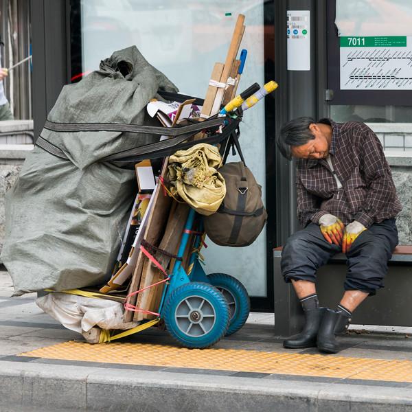 Man napping near a garbage cart, Seoul, South Korea