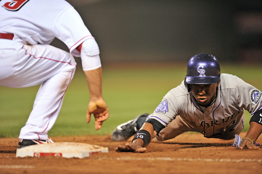 . Jonathan Herrera #18 of the Colorado Rockies gets back to first base safely on a pick off attempt in the seventh inning against the Cincinnati Reds at Great American Ball Park on June 4, 2013 in Cincinnati, Ohio. Colorado defeated Cincinnati 5-4.  (Photo by Jamie Sabau/Getty Images)