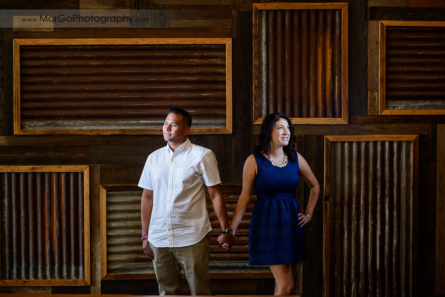 portrait of woman in blue dress and man in white shirt on wooden wall looking in the opposite direction during engagement session at San Pedro Square Market in San Jose