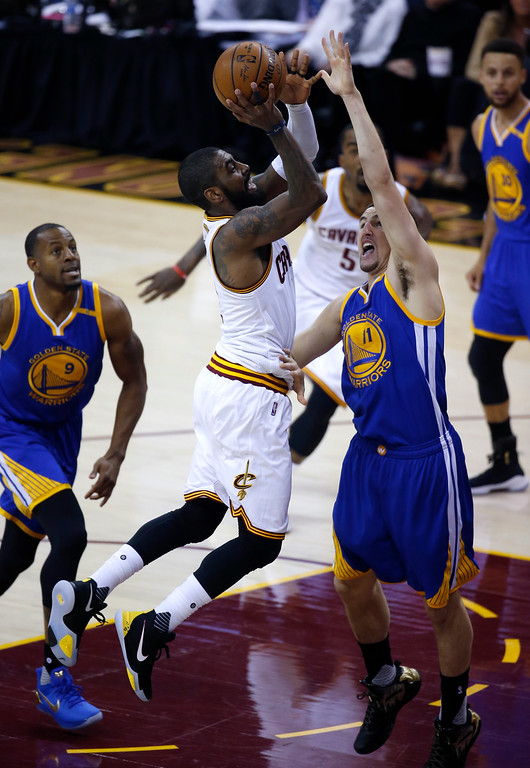 . Cleveland Cavaliers guard Kyrie Irving, center, drives on Golden State Warriors guard Klay Thompson (11) during the first half of Game 3 of basketball\'s NBA Finals in Cleveland, Wednesday, June 7, 2017. (AP Photo/Ron Schwane)