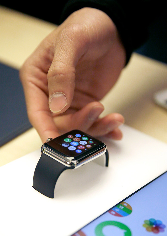 . A customer examines Apple\'s new watch at an Apple store in San Francisco, Friday, April 10, 2015. Apple has started taking orders for the watch on its website and the Apple Store app. Currently, that\'s the only way Apple is selling the watch, with shipments scheduled to start April 24. (AP Photo/Eric Risberg)
