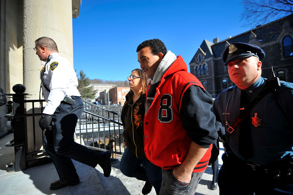 . Sandrino Oliver (center), uncle of missing 5-year-old Jeremiah Oliver of Fitchburg, is escorted back into Fitchburg District Court after a verbal outbreak that started in the courtroom following the competency hearing of Elsa Oliver, Friday. Left of Sandrino is Rose Valcourt, Jeremiah\'s paternal aunt. SENTINEL & ENTERPRISE / BRETT CRAWFORD