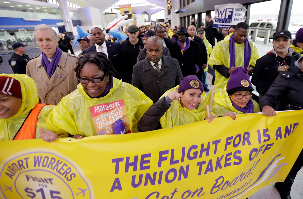 . Newark Mayor Ras Baraka, center, marches with service workers asking for $15 minimum wage pay during a rally at Newark Liberty International Airport, Tuesday, Nov. 29, 2016, in Newark, N.J. The event was part of the National Day of Action to Fight for $15. The campaign seeks higher hourly wages, including for workers at fast-food restaurants and airports. (AP Photo/Julio Cortez)
