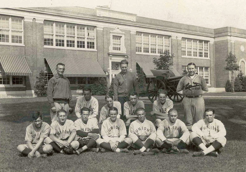 The Union Cardinals Baseball Team in front of the old UHS with canon and fancy awnings in the background.