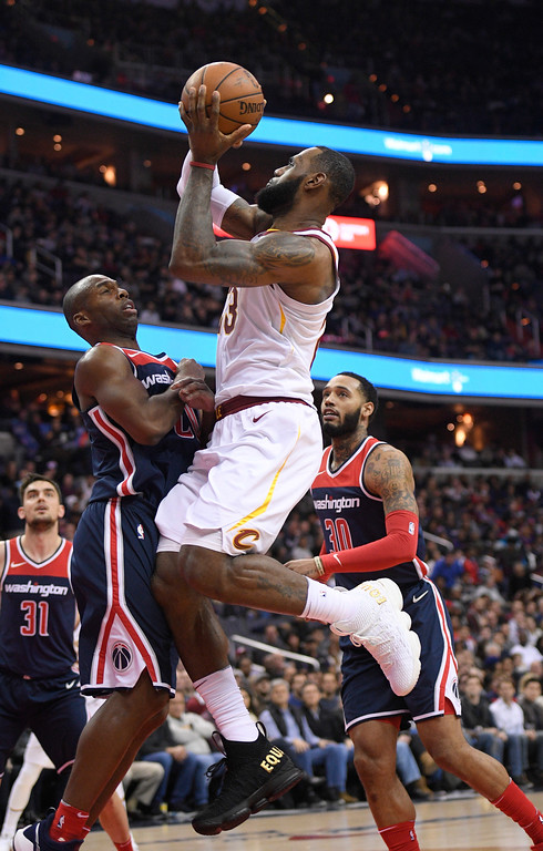 . Cleveland Cavaliers forward LeBron James (23) goes to the basket against Washington Wizards guard Jodie Meeks, left, and forward Mike Scott (30) during the first half of an NBA basketball game, Sunday, Dec. 17, 2017, in Washington. (AP Photo/Nick Wass)
