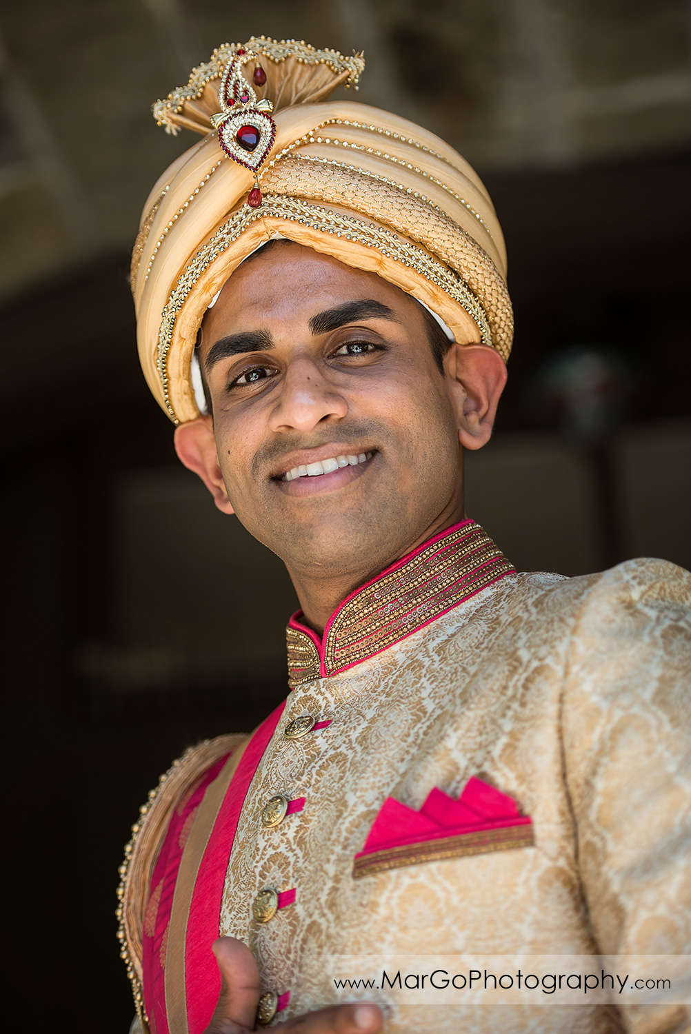 Indian groom wearing golden and pink sherwani and safa at Elliston Vineyards in Sunol