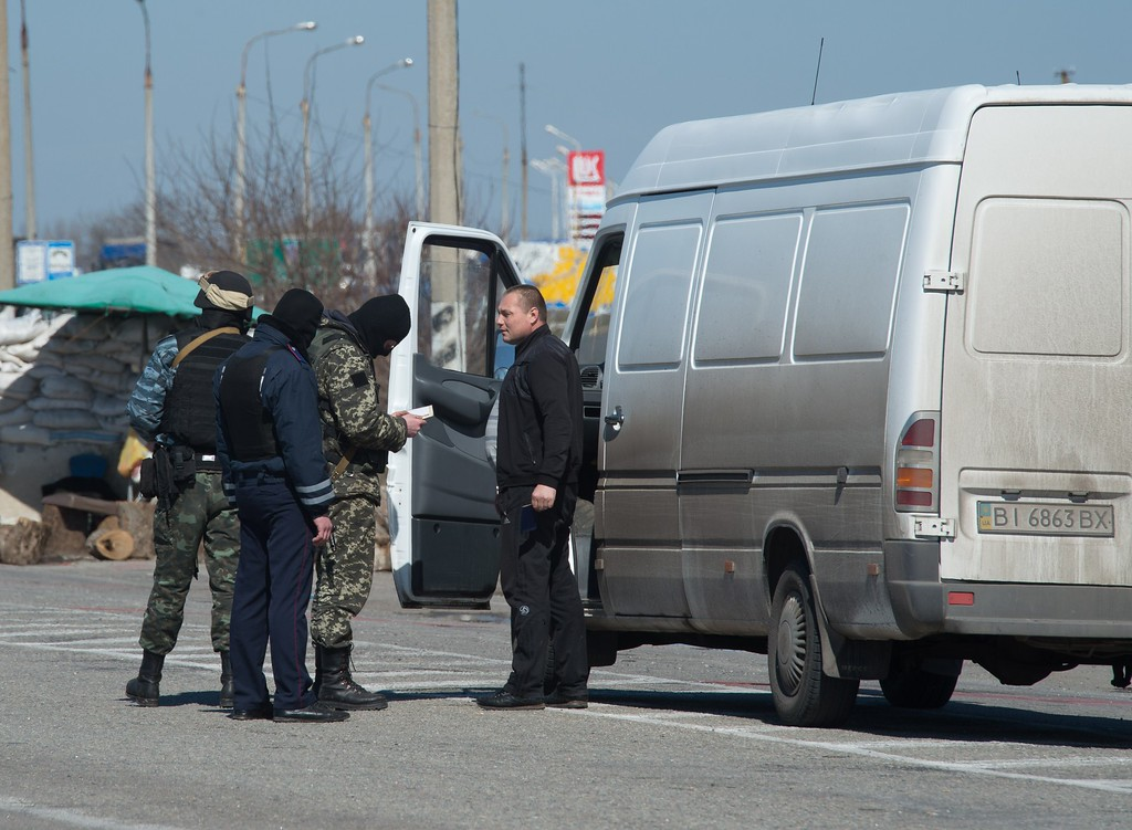 . Russian soldiers check documents and search cars at the check-point in the Henichesk district, on the road across the Chongar strait, one of the two roads linking Crimea to Ukraine on March 21, 2014. UN chief Ban Ki-moon said today the Ukrainian crisis can only be resolved through a diplomatic solution that respects the territorial integrity of the splintered ex-Soviet state. AFP PHOTO / DMITRY  SEREBRYAKOV/AFP/Getty Images