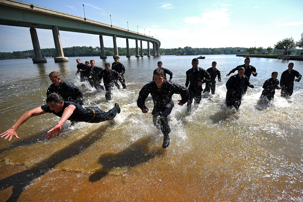 . Members of the United States Naval Academy freshman class race to the sand at the wet and sandy station during the annual Sea Trials training exercise at the U.S. Naval Academy on May 13, 2014 in Annapolis, Maryland. (Photo by Patrick Smith/Getty Images)