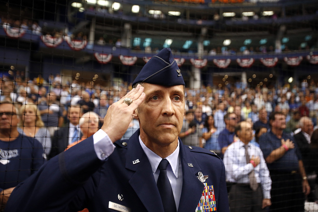 . Colonel Scott V. DeThomas, Commander, 6th Mobility Wing, MacDill Air Force Base, salutes the flag as he joins the Tampa Bay Rays and the Toronto Blue Jays stand for the national anthem before taking to the field to throw out the ceremonial first pitch during Opening Day ceremonies at the start of a game on March 31, 2014 at Tropicana Field in St. Petersburg, Florida.  (Photo by Brian Blanco/Getty Images)