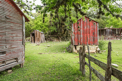 Three abandoned shacks with wooden fence
