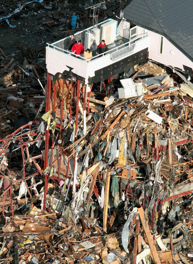 . People wait for rescue on the rooftop of a ruined building tangled with tsunami-drifted debris in Rikuzentakada, Iwate Prefecture, Saturday morning, March 12, 2011 after Japan\'s biggest recorded earthquake slammed into its eastern coast Friday. (AP Photo/Kyodo News)