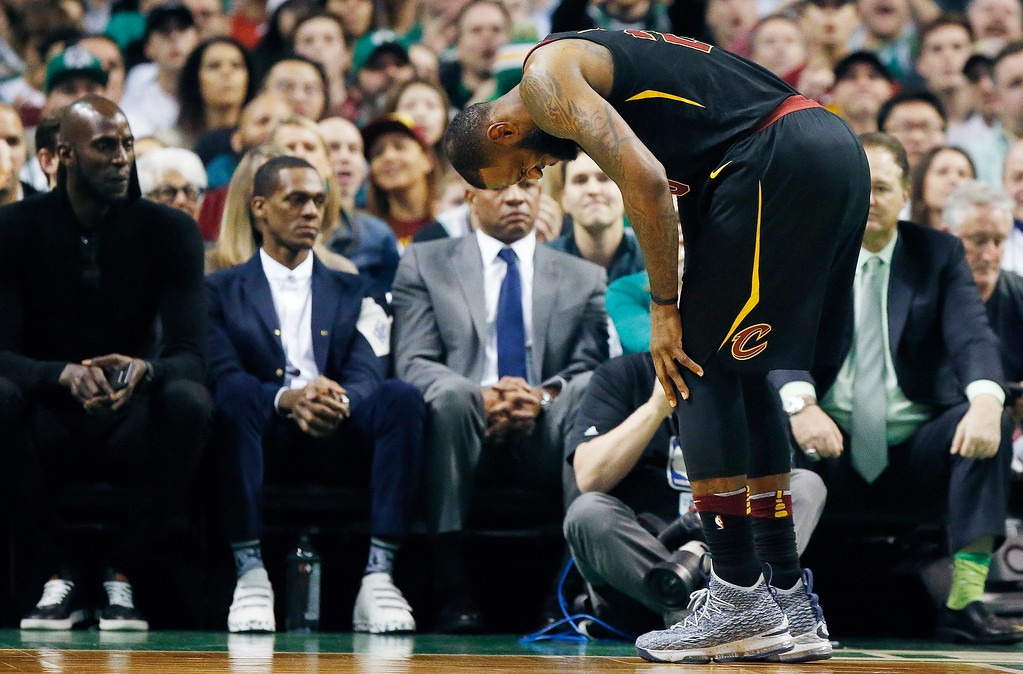 . Cleveland Cavaliers\' LeBron James holds his leg in front of former Boston Celtics\' Kevin Garnett, left, Rajon Rondo, second from left, and former head coach Doc Rivers, center, during the first quarter of an NBA basketball game against the Celtics in Boston, Sunday, Feb. 11, 2018. The Cavaliers won 121-99. (AP Photo/Michael Dwyer)