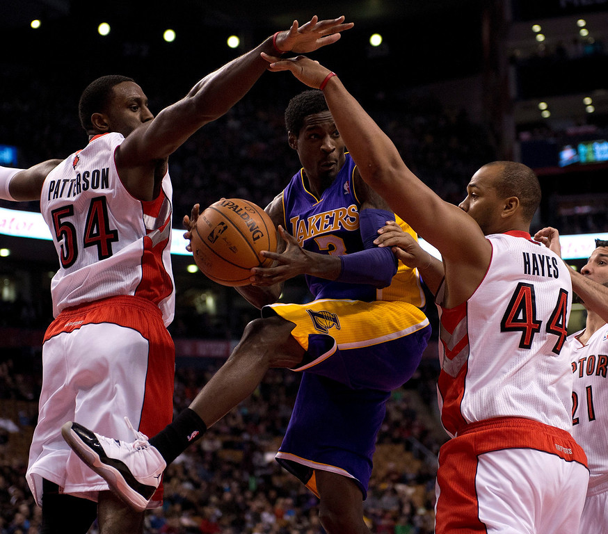 . Los Angeles Lakers guard Manny Harris (3) tries to pass the ball as he drives between Toronto Raptors forwards Patrick Patterson (54) and Chuck Hayes (44) during first-half NBA basketball game action in Toronto, Sunday, Jan. 19, 2014. (AP Photo/The Canadian Press, Frank Gunn)