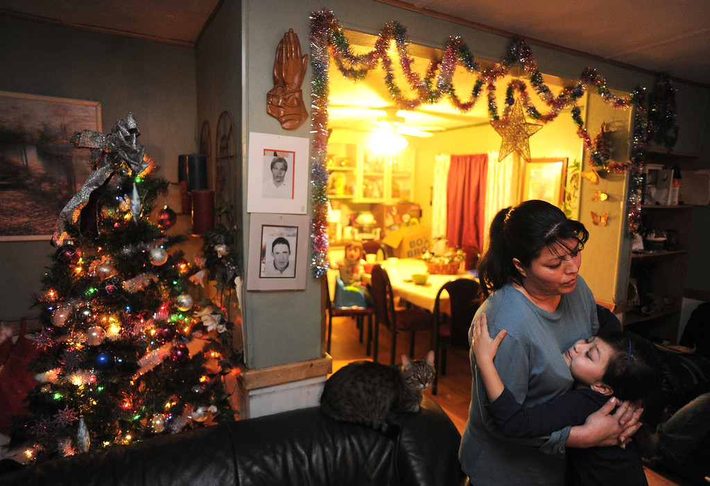 . GREELEY, CO - DECEMBER 16, 2013:  Rosario Moreno gets a hug from her daughter Yanna, 8, after dinner in the living room Meza\'s tiny home in Greeley, CO on December 16, 2013. She was sad because a loan she was hoping to receive to buy a new trailer didn\'t come through.   The Meza family, which consists of four children, Norma and her husband Martin have taken in the Moreno family after they lost everything in the September floods.  Rosario and her husband Jose have 5 children and are without a home at the moment.  Norma says she will help out her best friend for as long as she needs to.  The tiny house has 3 bedrooms and 2 small bathrooms and is home now to 14 people, 2 cats and 3 dogs.  (Photo By Helen H. Richardson/ The Denver Post)