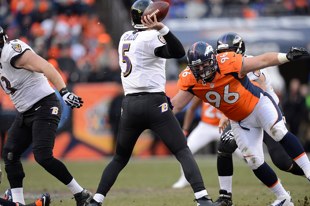 Description of . Denver Broncos defensive tackle Mitch Unrein (96) moves in on Baltimore Ravens quarterback Joe Flacco (5) in the second quarter. The Denver Broncos vs Baltimore Ravens AFC Divisional playoff game at Sports Authority Field Saturday January 12, 2013. (Photo by Joe Amon,/The Denver Post)