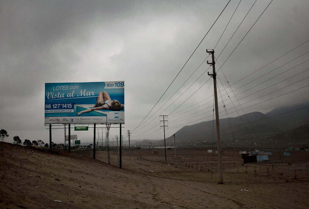 ". In this Aug. 1, 2013 photo, a billboard advertising ocean view lots is seen next to the Pan-American highway in the outskirts of Lima, Peru. For roughly four months a year, the sun abandons Peru\'s seaside desert capital, suffocating it under a ponderous gray cloudbank and fog that coats the city with nighttime drizzles. The cold Humboldt current that runs north from Antarctica along the coast is the culprit, colliding with the warmer tropical atmosphere to create the blinding mists called ""garua\"" in coastal Chile and Peru. (AP Photo/Rodrigo Abd)"