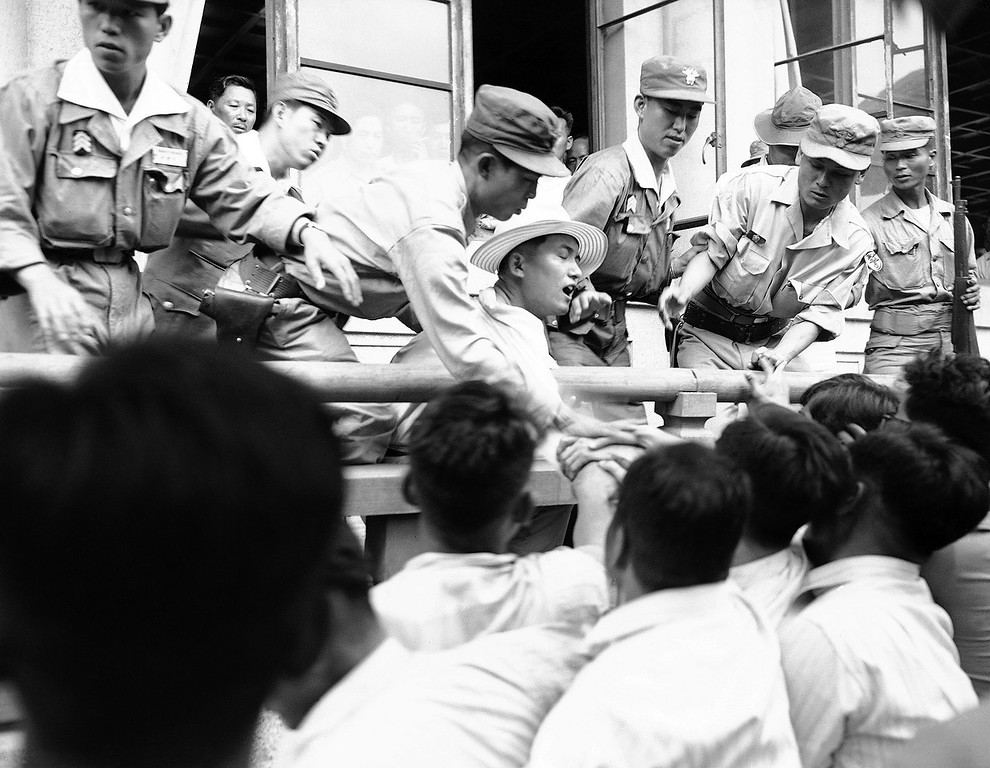 . Republic of South Korea policemen come to the aid of an assemblyman (wearing straw hat) being attacked by supporters of President Syngman Rhee. The demonstrators, who were demanding that the assembly give into Rhee or dissolve itself, closed in on the law maker as he tried to leave the National Assembly Hall in Pusan, June 28, 1952. (AP Photo/FW)