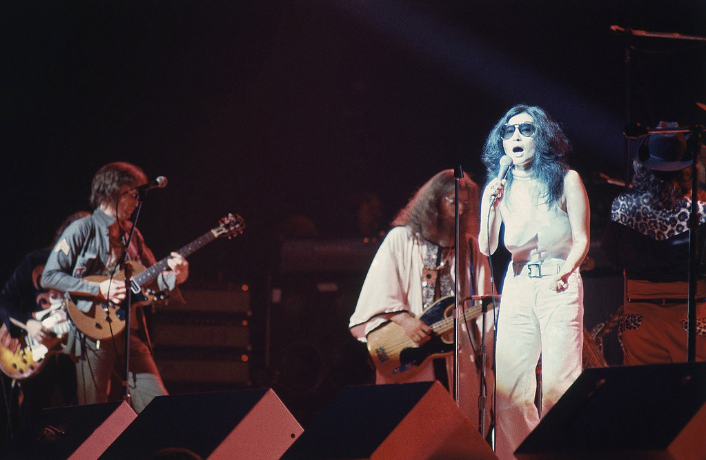 """. Former Beatle John Lennon\'s wife Yoko Ono, right, performs during \""""One To One\"""", a charity concert to benefit mentally challenged children, at New York\'s Madison Square Garden, Aug. 30, 1972. Lennon plays guitar at far left. (AP Photo/Dave Pickoff)"""
