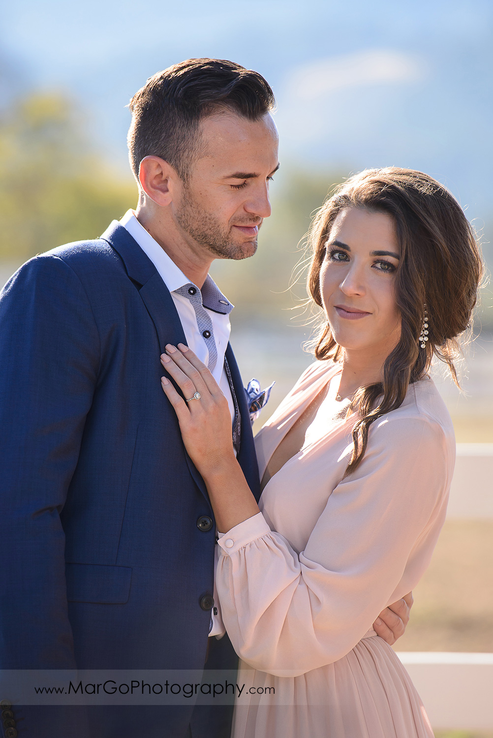 portrait of man in blue suit looking at woman in pink dress looking into camera during Napa Valley engagement session at Tamber Bey Vineyards in Calistoga