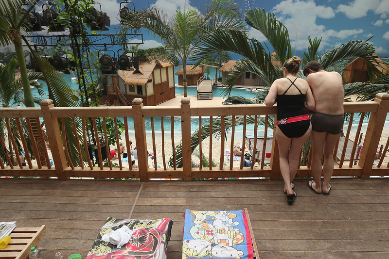 ". Visitors look down from a deck above the ""South Sea\"" beach at the Tropical Islands indoor resort on February 15, 2013 in Krausnick, Germany. Located on the site of a former Soviet military air base, the resort occupies a hangar built originally to house airships designed to haul long-distance cargo. Tropical Islands opened to the public in 2004 and offers visitors a tropical getaway complete with exotic flora and fauna, a beach, lagoon, restaurants, water slide, evening shows, sauna, adventure park and overnights stays ranging from rudimentary to luxury. The hangar, which is 360 metres long, 210 metres wide and 107 metres high, is tall enough to enclose the Statue of Liberty.  (Photo by Sean Gallup/Getty Images)"