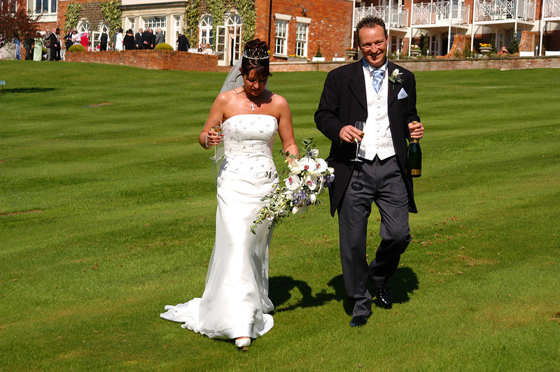 Wedding Couple strolling with Champagne in the grounds of The Chewton Glen Hotel,Hampshire