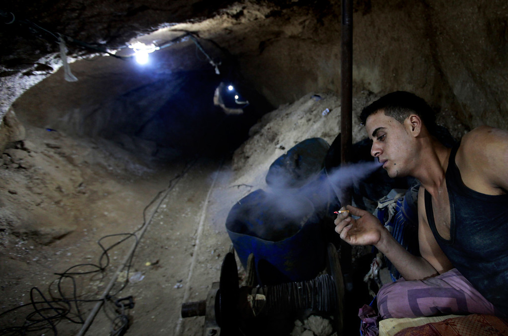 . In this Monday, Sept. 30, 2013 photo, a Palestinian worker smokes a cigarette inside a smuggling tunnel along the border with Egypt in Rafah, southern Gaza Strip. Gazaís tunnel smugglers along the border with Egypt are mostly idle these days. Some rest on cots in the dank underground pathways, stretching out for a smoke. Others pass the time cleaning the small carts on wheels that are normally pulled through the tunnels carrying cement or consumer goods from Egypt. Since the summer, Egyptís military has tried to destroy or seal off most of the smuggling tunnels under the Gaza-Egypt border, a consequence of the heightened tensions between Cairo and the Hamas government in Gaza. (AP Photo/Hatem Moussa)