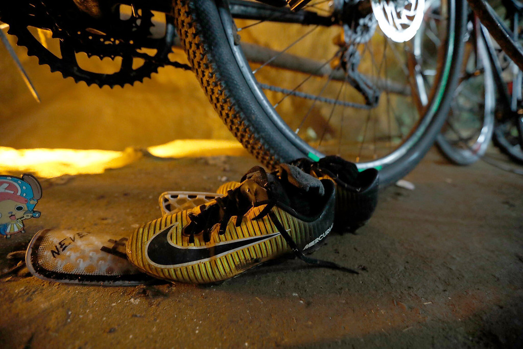 . A pair of soccer shoes are left next to bicycles from a group of missing boys at the entrance of a deep cave in Chiang Rai, northern Thailand, Monday, June 25, 2018. Officials say multiple attempts to locate the 12 boys and their soccer coach missing in a flooded cave in northern Thailand for nearly two days have failed, but that they will keep trying. (Thai News Pix via AP)