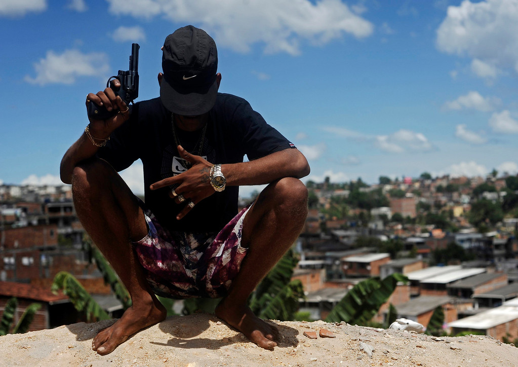 . A Brazilian drug gang member nicknamed Firecracker, 22, poses with a gun atop a hill overlooking a slum in Salvador, Bahia State, April 11, 2013. One of Brazil\'s main tourist destinations and a 2014 World Cup host city, Salvador suffers from an unprecedented wave of violence with an increase of over 250% in the murder rate, according to the Brazilian Center for Latin American Studies (CEBELA). Picture taken April 11, 2013.  REUTERS/Lunae Parracho