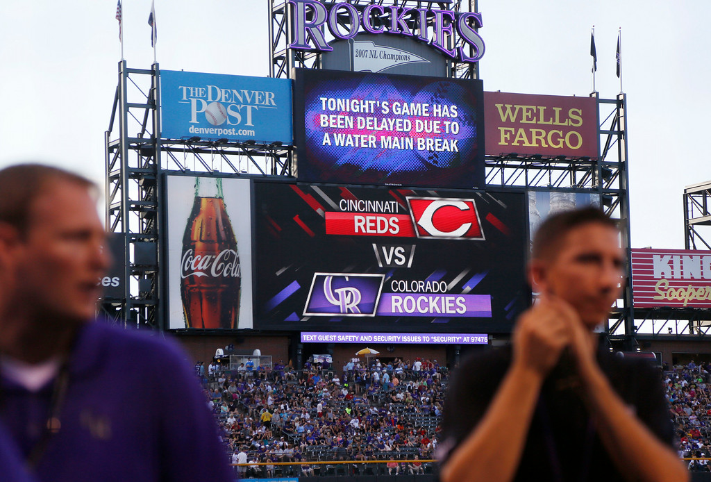 . Workers toil on the field as the outfield scoreboard displays notice that a water main break has forced the delay of a baseball game between the Cincinnati Reds and the Colorado Rockies in Denver on Saturday, Aug. 16, 2014. The game was eventually canceled and will be made up as part of a split doubleheader on Sunday. (AP Photo/David Zalubowski)