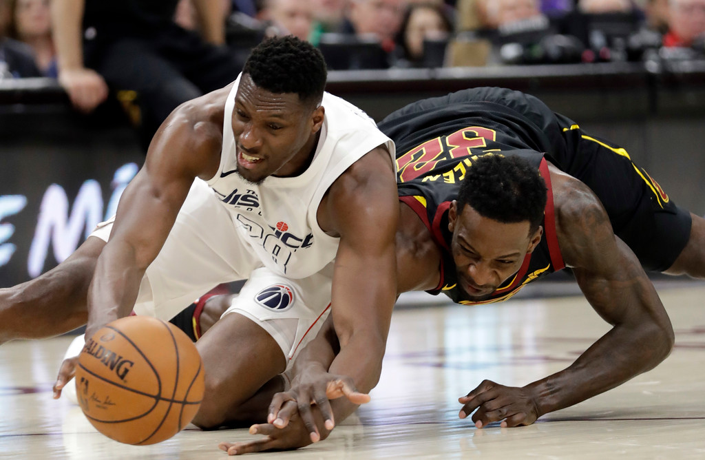 . Washington Wizards\' Ian Mahinmi, left, from France, and Cleveland Cavaliers\' Jeff Green battle for the ball in the first half of an NBA basketball game, Thursday, April 5, 2018, in Cleveland. (AP Photo/Tony Dejak)