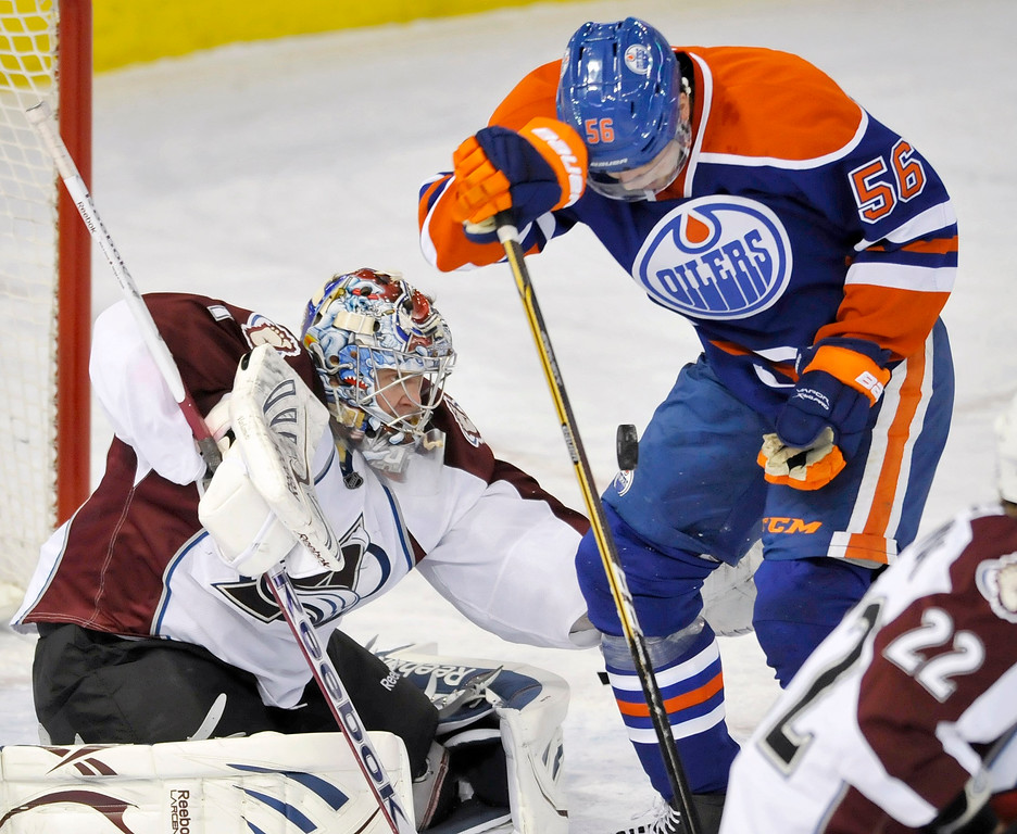 . Colorado Avalanche goalie Semyon Varlamov (L) and Edmonton Oilers\' Teemu Hartikainen battle for the puck during the first period of their NHL hockey game in Edmonton January 28, 2013.  REUTERS/Dan Riedlhuber